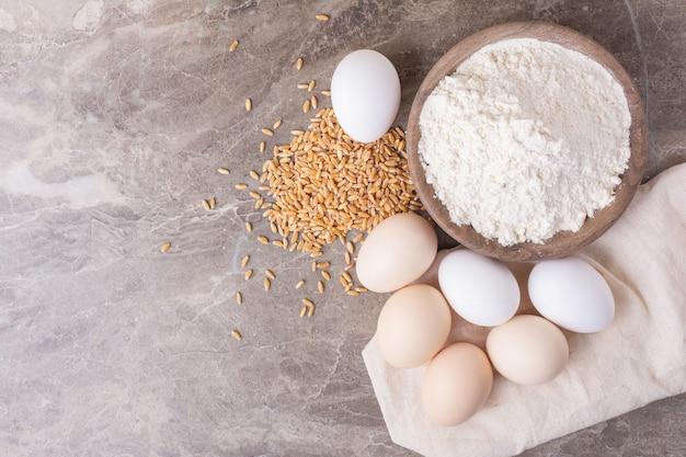 Uova in una tazza bianca su grigio.