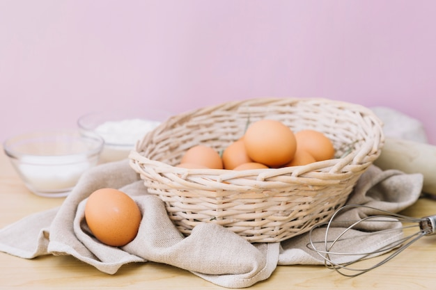 Eggs in wicker basket and whisks on wooden desk