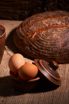 Eggs with bread and kitchen utensils on vintage wood