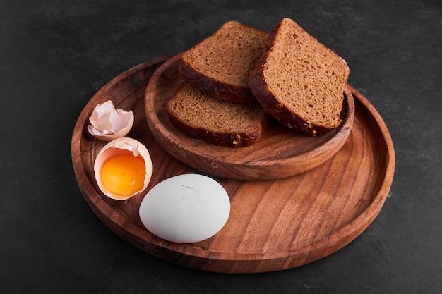 나무 접시에 빵 조각과 계란.