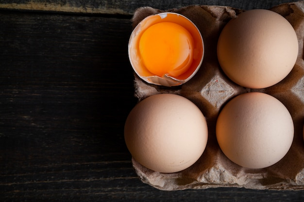 Eggs with broken one top view on a dark wooden background space for text