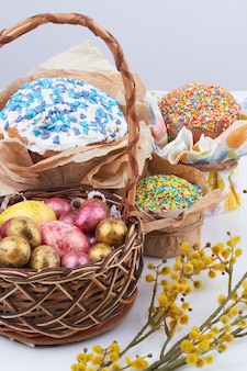 ケーキの垂直ショットと卵。白い背景の上のイースターシンボル構成。