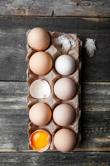 Eggs with cracked ones top view on a dark wooden background, vertical