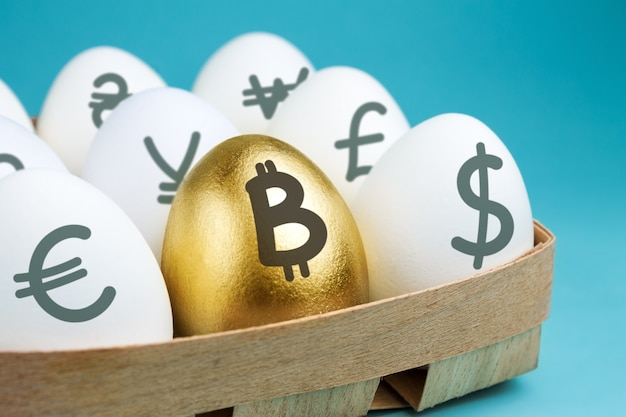 Eggs with currency signs in wooden packing and golden egg with a bitcoin sign