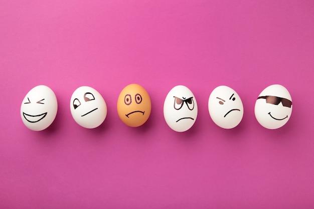 Яйца с разными эмоциями на лице. пасхальная композиция с копией пространства на розовом фоне.