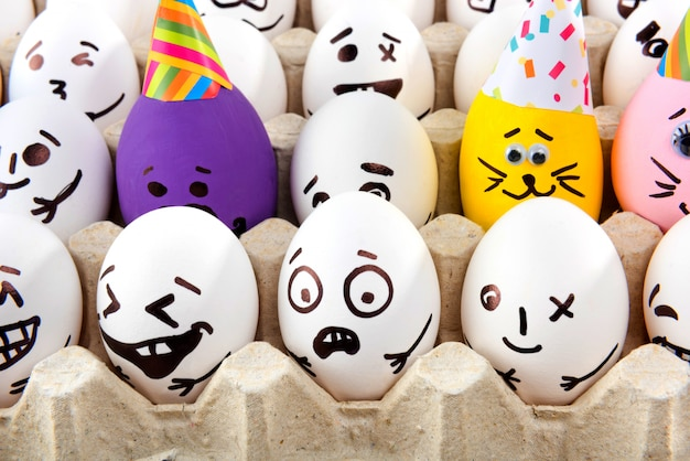 Eggs with drawn cartoon faces in tray.