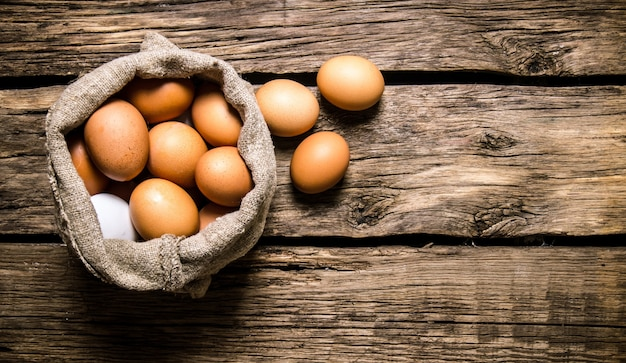 Eggs with an old bag. on a wooden table. free space for text . top view