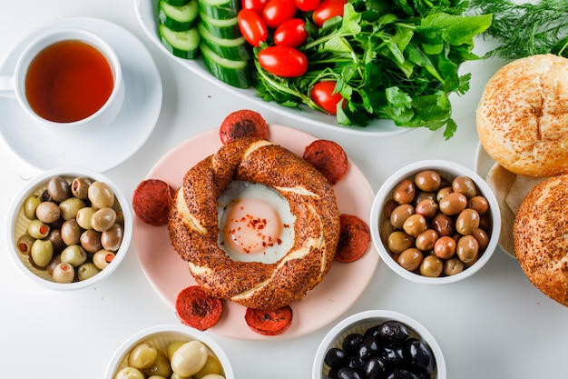 Eggs with sausage in a plate with a cup of tea, turkish bagel, salad top view on a white surface