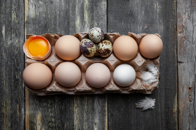 Eggs with small ones top view on a dark wooden background