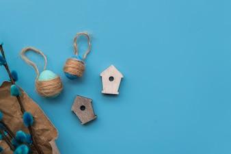 Яйца с нитками возле веток ивы и декоративный птичий домик