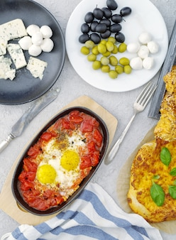 Eggs with tomatoes, cheese, olives and bread