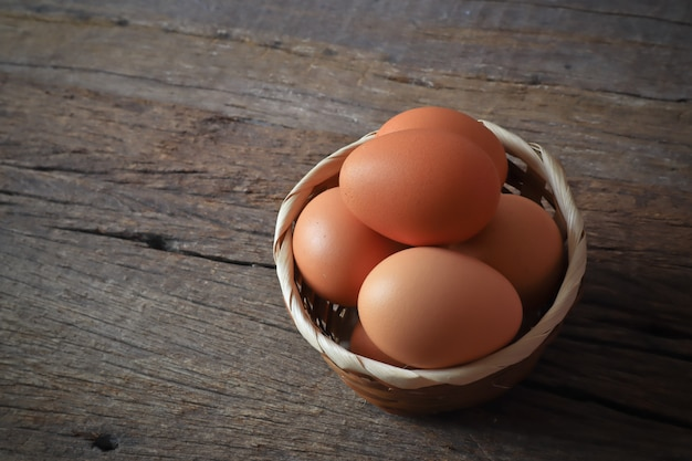 Eggs in the wood basket on the wood table