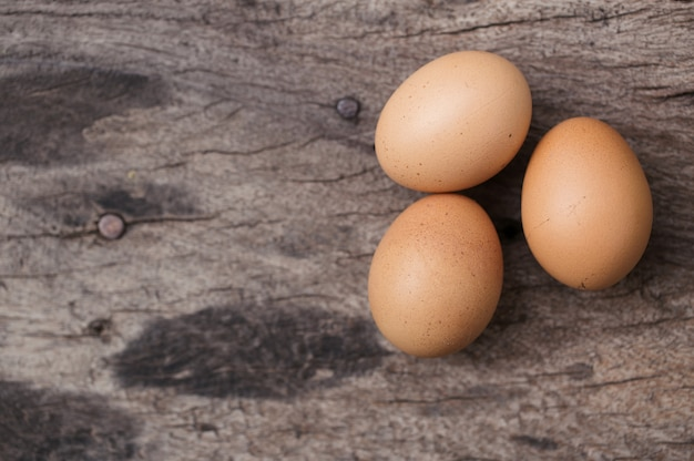Eggs on wood table background with space for text.