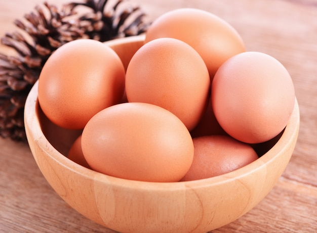 Eggs in wooden bowl on wooden background