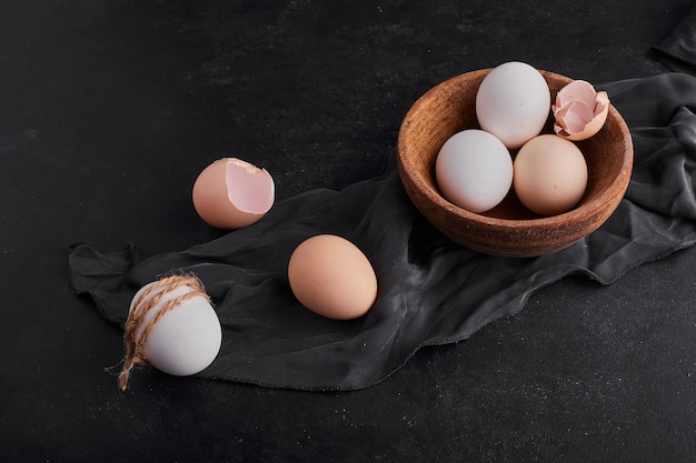 Uova in una tazza di legno su un canovaccio da cucina nero.