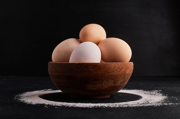 Eggs in a wooden cup on black space.