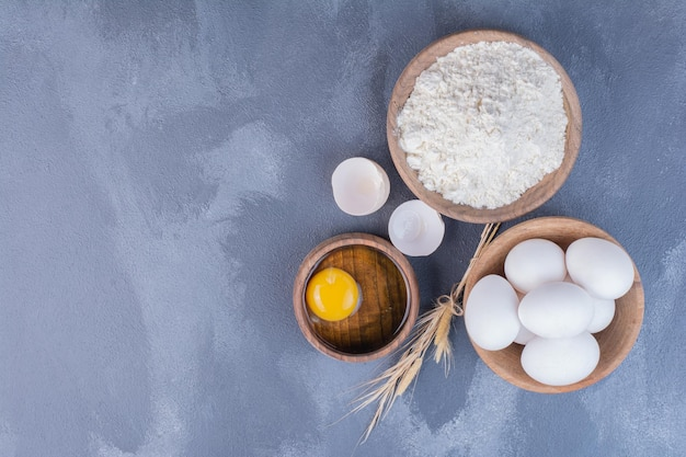 Eggs and a yellow yolk in a wooden cup.