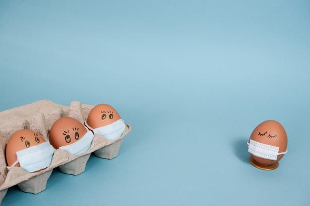 코로나바이러스 전염병으로 인한 달걀 껍질 의료 마스크와 집에서 격리된 부활절 휴일