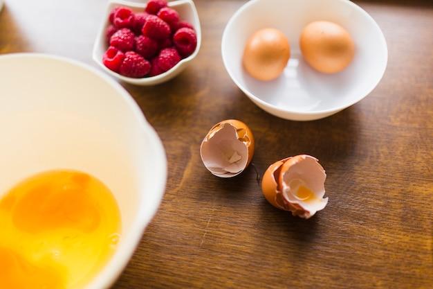 Eggshell near bowl with raw eggs