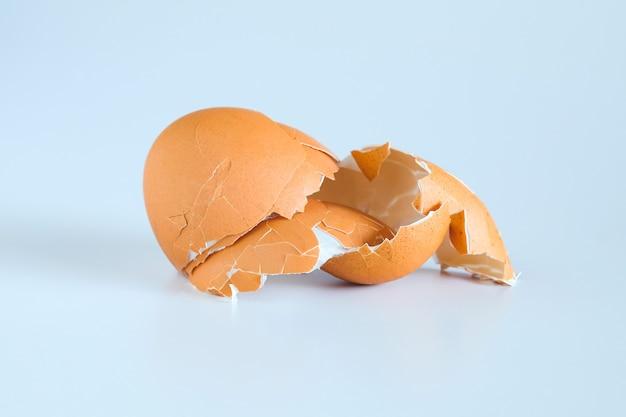 Яичная скорлупа разбросана из яйца, сваренного на белом фоне.