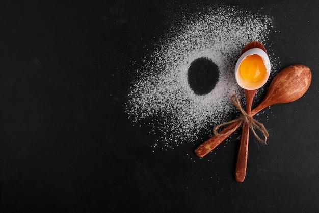 Guscio d'uovo in un cucchiaio di legno sulla superficie della farina, vista dall'alto.