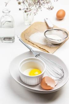 달걀 껍질, 노른자 및 세라믹 그릇에 털어냅니다. 종이에 밀가루와 체. 계란과 물병. 평면도