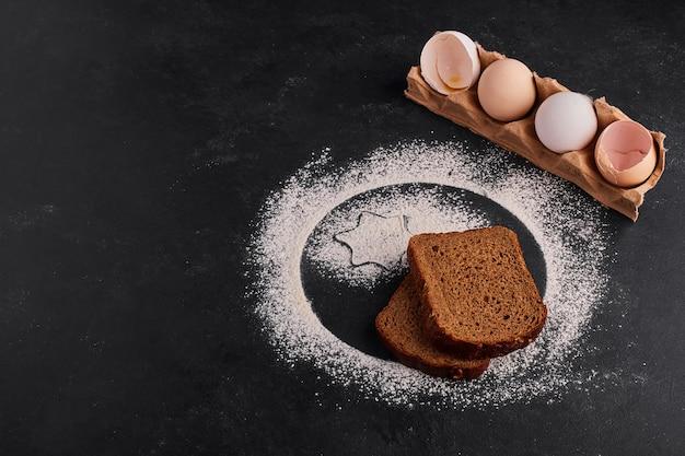 Gusci d'uovo e fette di pane sulla superficie nera.