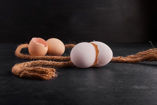黒い表面に分離された卵殻。