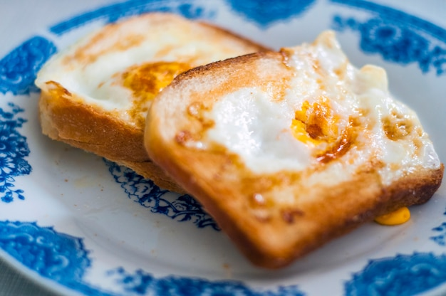 自然光で撮影されたプレートの卵パン。バターと卵のゴールデンフレンチトースト。パンと朝食。英語の朝食。卵と健康的な朝食。おいしい朝食