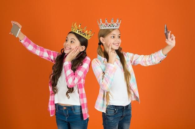 자기중심적인 공주님. 아이들은 황금 왕관을 상징하는 공주를 입는다. 버릇없는 아이의 경고 신호. 버릇없는 아이를 키우지 마십시오. 셀카 사진 스마트폰 카메라를 복용하는 여자. 버릇없는 어린이 개념.