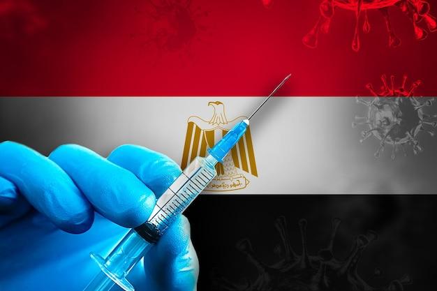 이집트 코비드19 예방 접종 캠페인 파란색 고무 장갑을 끼고 깃발 앞에 주사기를 들고 있습니다