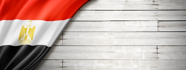 Egypt flag on old white wall. horizontal panoramic banner.
