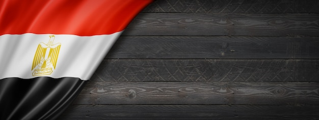 黒い木の壁にエジプトの旗。水平方向のパノラマバナー。