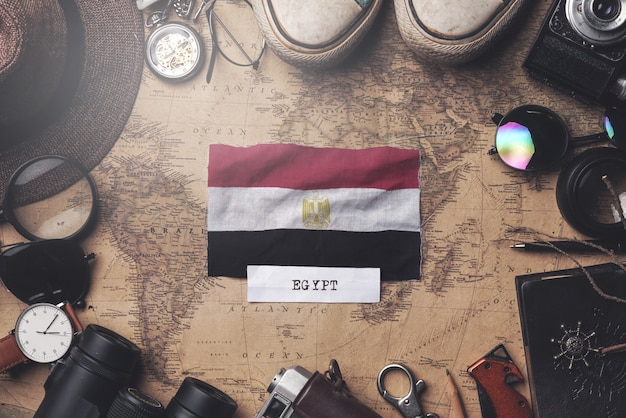 Egypt flag between traveler's accessories on old vintage map. overhead shot