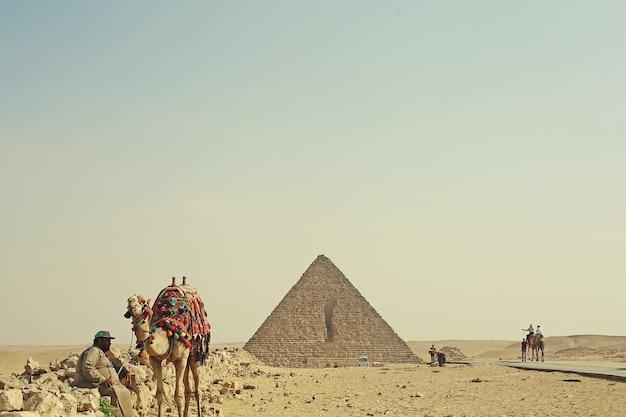 ピラミッド、ラクダ、男性とエジプトの砂漠の風景