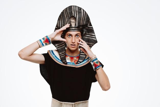 Uomo egiziano faraone in antico costume egiziano guardando davanti confuso e sorpreso in piedi sul muro bianco