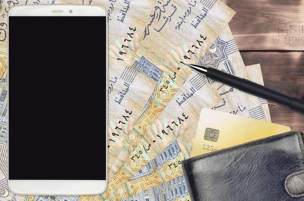 Купюры египетских пиастров и смартфон с кошельком и кредитной картой