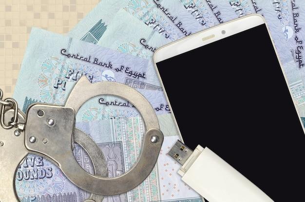 Купюры египетских фунтов и смартфон с полицейскими наручниками