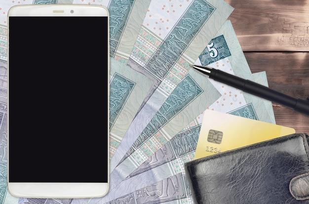Банкноты египетских фунтов и смартфон с кошельком и кредитной картой