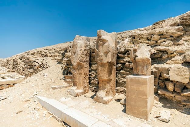 ジェゼル王のピラミッドの近くにあるファラオのエジプトの彫像。エジプトの神殿の大きなブロックと断片。