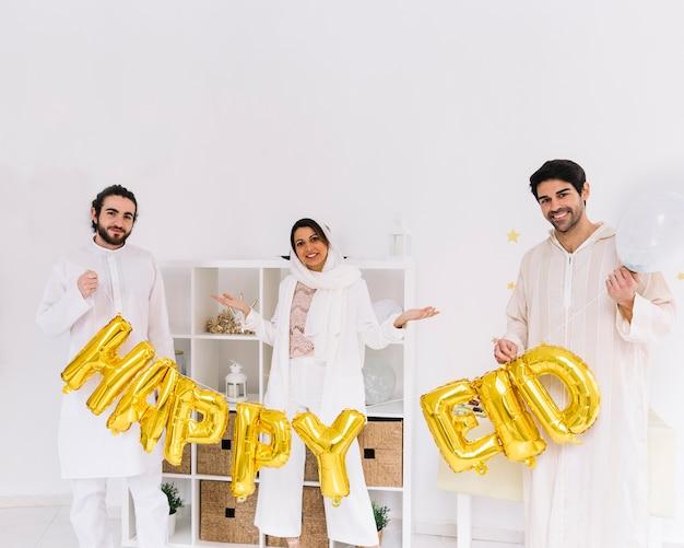 Концепция eid al-fitr с друзьями, показывающими буквы
