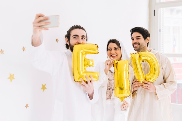 Eid al-fitr concept with friends showing letters