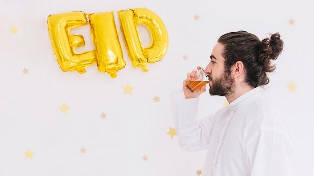 Concetto di eid al-fitr con l'uomo che beve il tè