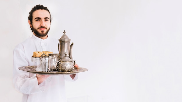 Eid al-fitr concept with man holding plate with tea