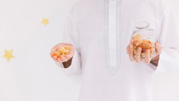 Concetto di eid al-fitr con l'uomo che presenta pasticceria araba