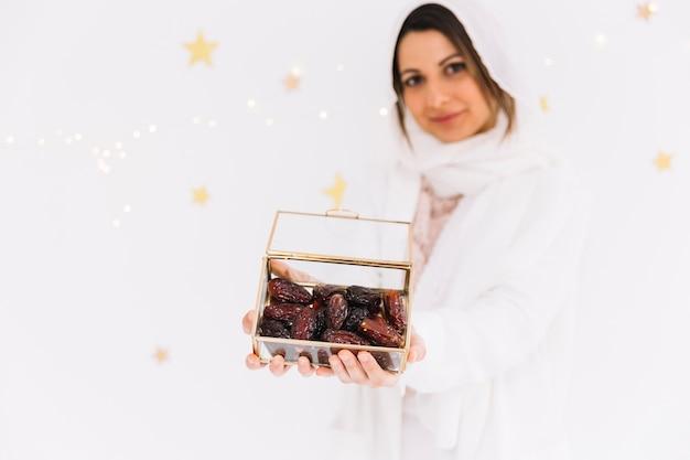 Eid al-fitr concept con donna musulmana che tiene scatola di datteri