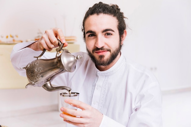 Eid al-fitr concept with tea and smiling man
