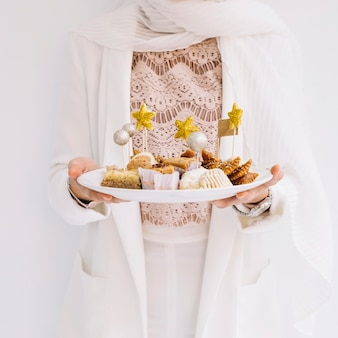 Eid concept with woman holding arab pastry
