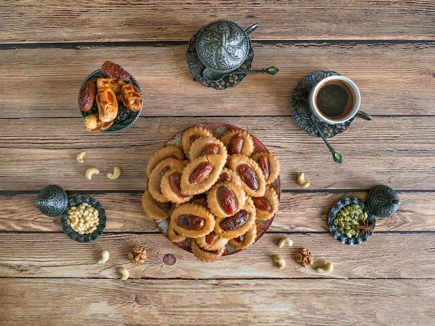 木製のテーブルにイードデートのお菓子。ラマダン食品テーブル。