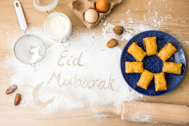Eid mubarak inscription on flour with eastern sweets on plate